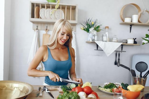 Fille belle et sportive dans une cuisine avec un légume Photo gratuit