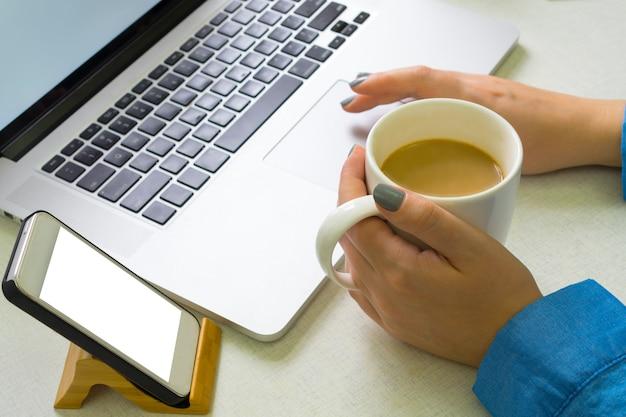 Fille bénéficie d'un ordinateur portable et boit du café Photo Premium