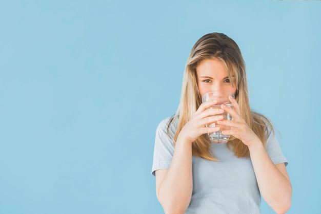 Fille blonde buvant un verre d'eau Photo gratuit