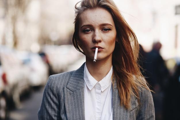 Fille blonde avec des cigares se trouve dans la rue Photo gratuit