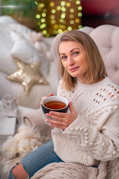 Fille blonde dans un pull avec une tasse de thé assise sur le lit Photo Premium