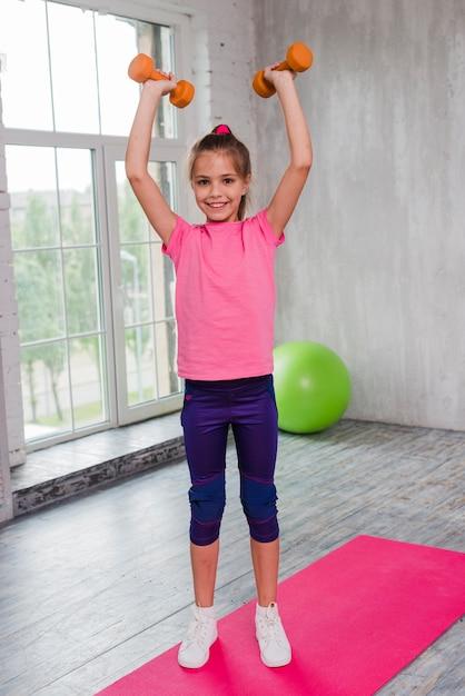 Une fille blonde, debout sur un tapis rose, exerçant avec haltère, regardant la caméra Photo gratuit