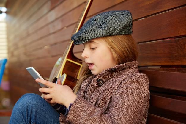 Fille blonde enfant jouant béret d'hiver smartphone Photo Premium