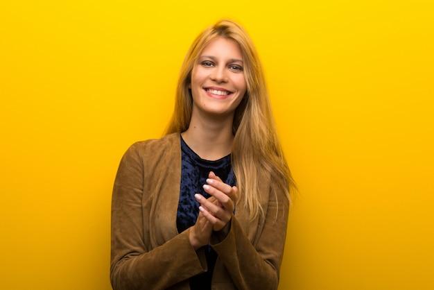 Fille blonde sur fond jaune vibrant applaudissant après une présentation à une conférence Photo Premium