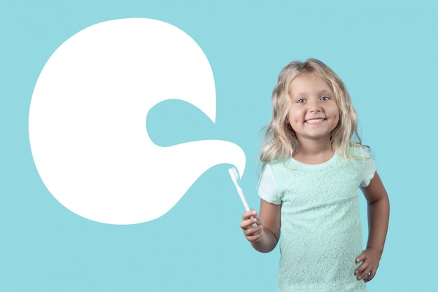 Une Fille Blonde Frisée Avec Un Sourire Montre Comment Se Brosser Les Dents. Photo Premium