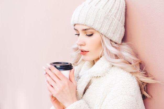 La fille blonde en habits d'hiver tient un café dans un gobelet en papier sur un fond rose. Photo Premium