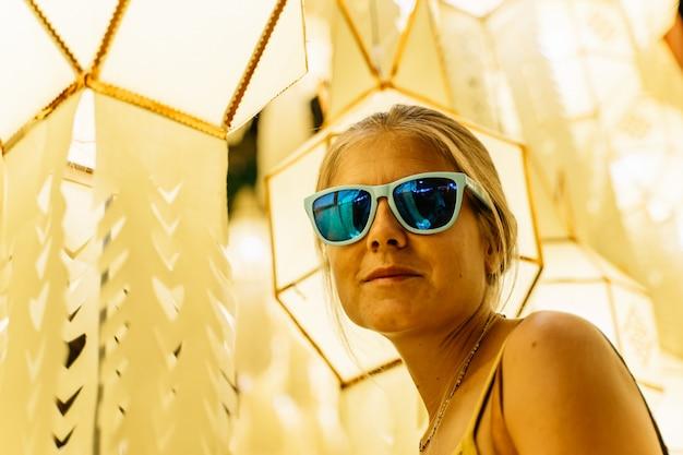 Fille blonde avec des lunettes de soleil entourée de lanternes chinoises dans la nuit Photo gratuit