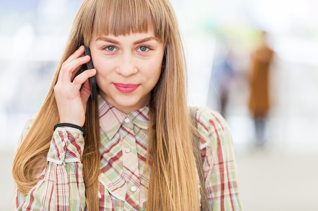 Fille blonde parlant au téléphone et regardant la caméra Photo Premium
