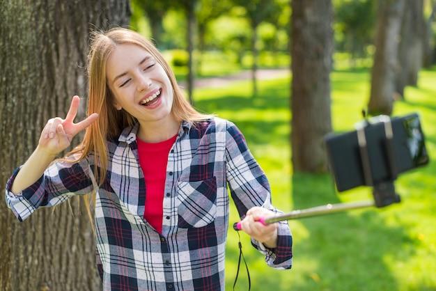 Fille Blonde Prenant Un Selfie à Côté D'un Arbre Photo gratuit