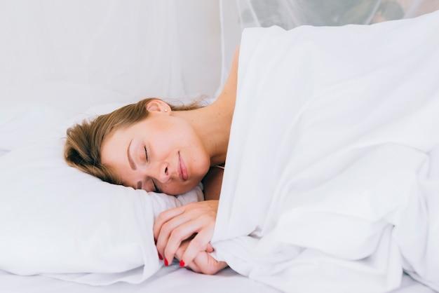 Fille blonde qui dort sur le lit Photo gratuit