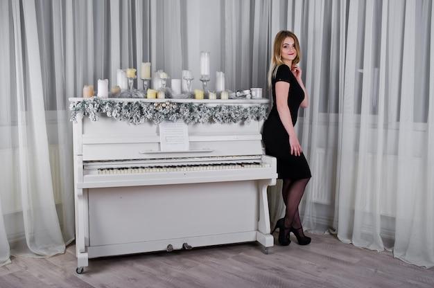 Fille Blonde En Robe Noire Posée Près Du Piano Avec Décor De Bougies De Noël En Salle Blanche. Photo Premium