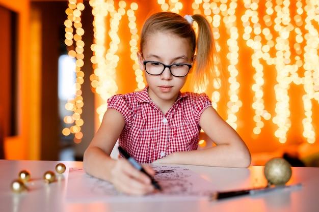 Fille blonde à la robe rose et grandes lunettes noires dessinant le père noël. thème de noël Photo Premium