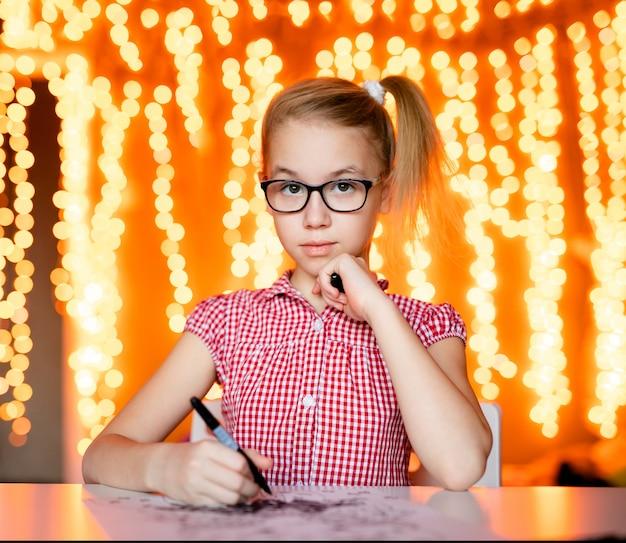 Fille blonde à la robe rose et grandes lunettes noires dessinant le père noël. thème de la nouvelle année Photo Premium