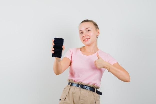 Fille Blonde Tenant Un Téléphone Portable, Montrant Le Pouce Vers Le Haut En T-shirt, Pantalon Et à La Joyeuse Vue De Face. Photo gratuit