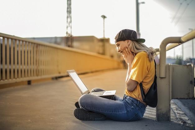 Fille blonde utilisant un ordinateur portable dans la rue Photo Premium