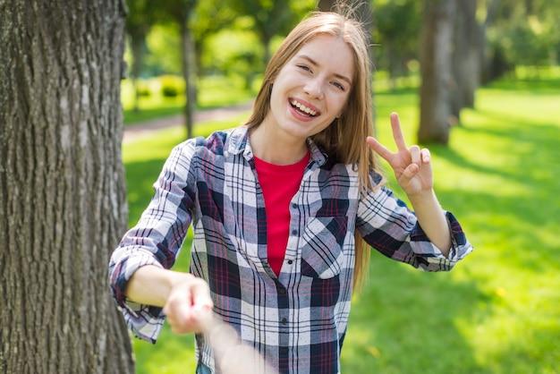 Fille blonde vue de face prenant un selfie à côté d'un arbre Photo gratuit