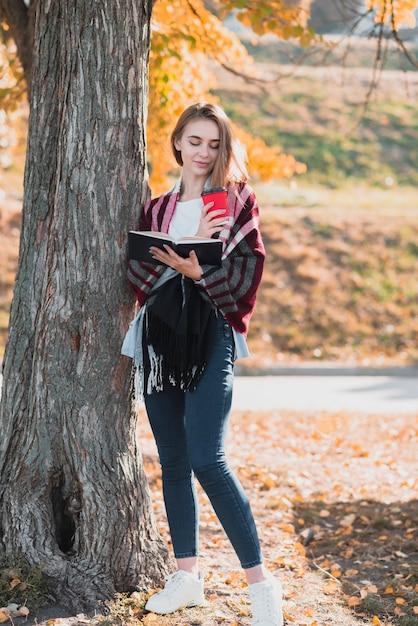 Fille blonde vue de face tenant un cahier Photo gratuit