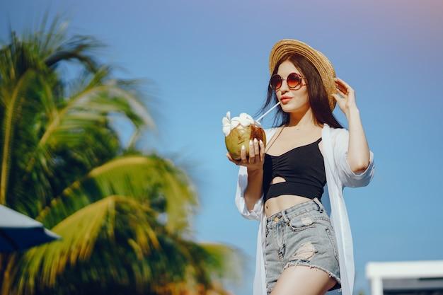 Fille, boire du jus frais d'une noix de coco au bord de la piscine Photo gratuit