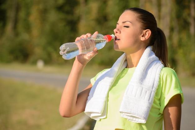 La fille boit de l'eau après avoir fait du jogging le matin. Photo Premium