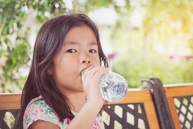 Fille Boit De L'eau D'une Bouteille Photo Premium