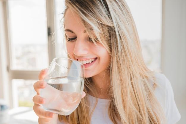 Fille en bonne santé, buvant un verre d'eau Photo gratuit