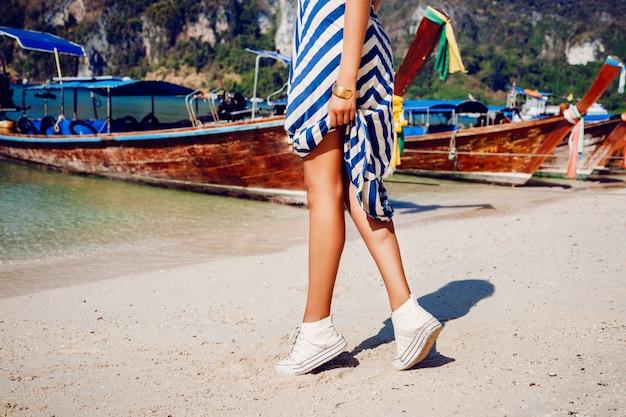 Fille En Bottes De Cuir Blanc Et Robe Longue Sautant Et Amusez-vous à La Belle Plage De Thaïlande. Photo gratuit