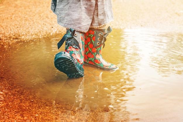Fille en bottes de pluie est debout dans une flaque d'eau Photo Premium