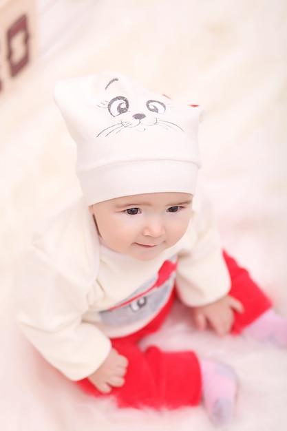 Fille bouclée mignonne enfant en bas âge, debout à une table de dîner de noël régler les plats en préparation pour célébrer noël Photo Premium
