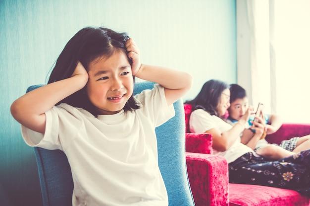 Fille Bouleversée Assise Sur Une Chaise Mère Profitant Avec Son Frère Du Canapé à La Maison Photo Premium