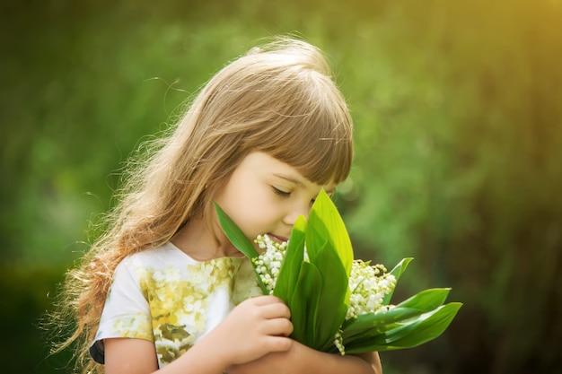 Fille avec un bouquet de lys de la vallée. mise au point sélective. Photo Premium