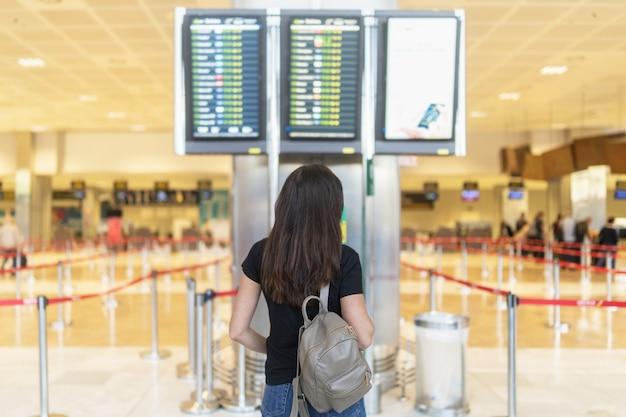 Fille brune aux cheveux longs en attente de départ à l'aéroport. Photo Premium