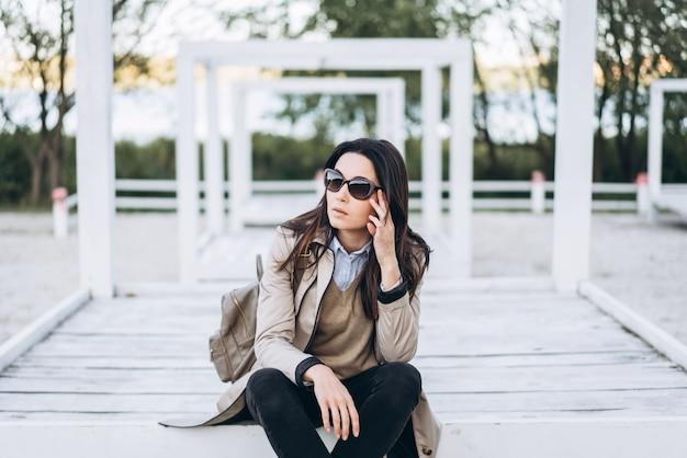 Fille brune de longs cheveux à lunettes de soleil se détendre en plein air. Photo Premium