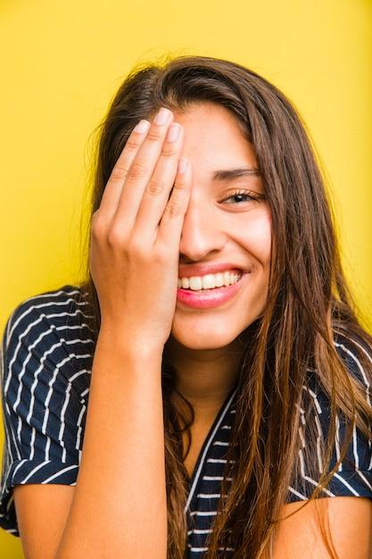 Fille brune avec la main sur le visage Photo gratuit