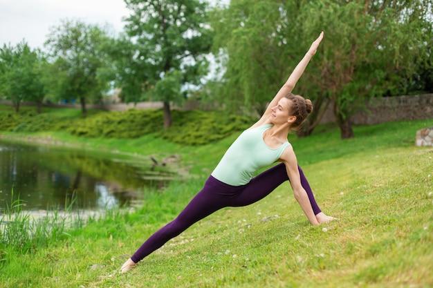 Fille brune mince, faire du yoga en été sur une pelouse verte au bord du lac Photo Premium