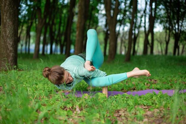 Fille Brune Mince Fait Du Sport Et Effectue Des Poses De Yoga Belles Et Sophistiquées Dans Un Parc D'été. Forêt Luxuriante Verte Sur La. Femme Faisant Des Exercices Sur Un Tapis De Yoga Photo Premium