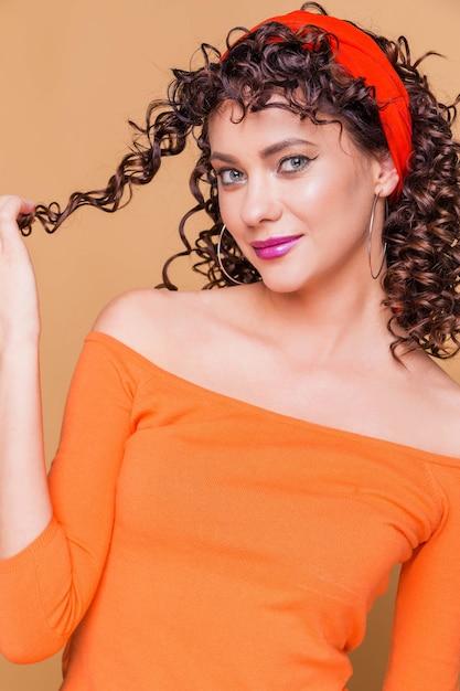 Fille Brune à La Mode Dans Un Pull Orange Vif Et En Bandana Posant Sur Orange Photo Premium