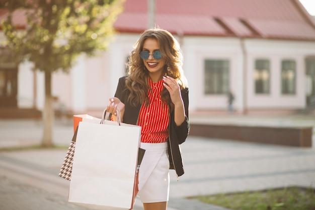 Fille Brune à La Mode Avec Des Sacs à Provisions En Papier Coloré, Marchant Dans La Rue. Photo Premium