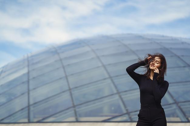 Fille brunetter à côté d'un immeuble moderne Photo gratuit