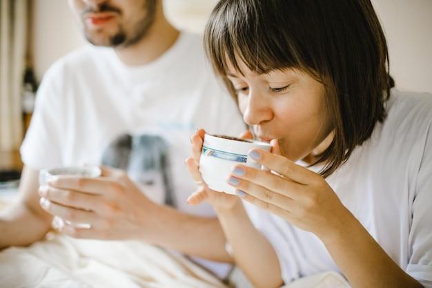 Fille buvant du café chaud le matin avec son petit ami Photo gratuit