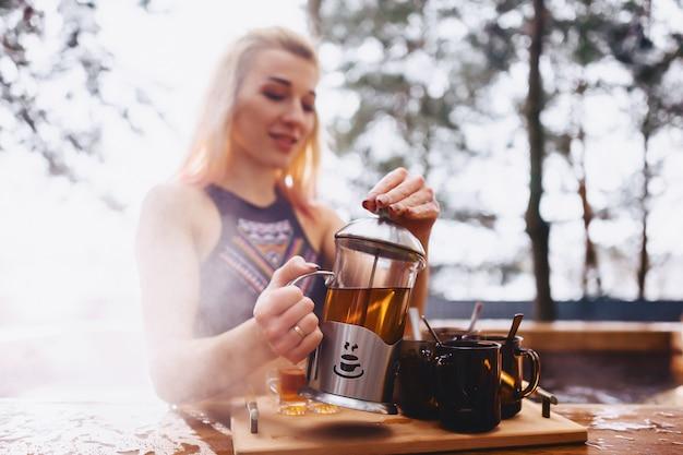 Fille buvant du thé chaud tout en restant assis en hiver Photo Premium