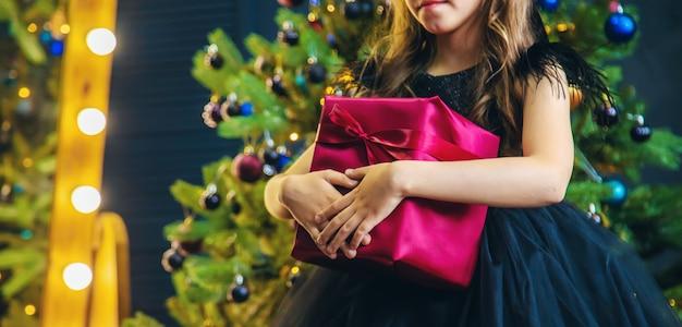 Fille avec des cadeaux dans la nuit de noël. Photo Premium