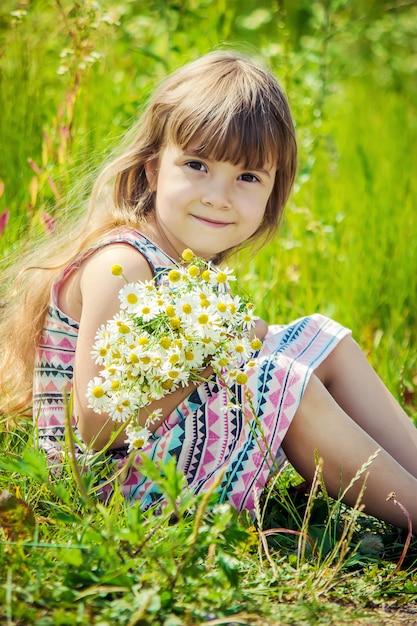 Fille à la camomille. mise au point sélective. fleurs nature. Photo Premium