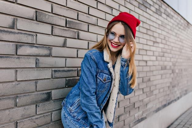 Fille Caucasienne Extatique En Tenue De Denim Et Lunettes Bleues Posant Avec Un Sourire Mignon. Heureux Jeune Femme Au Chapeau Rouge S'amuser Pendant Une Séance Photo De Rue. Photo gratuit