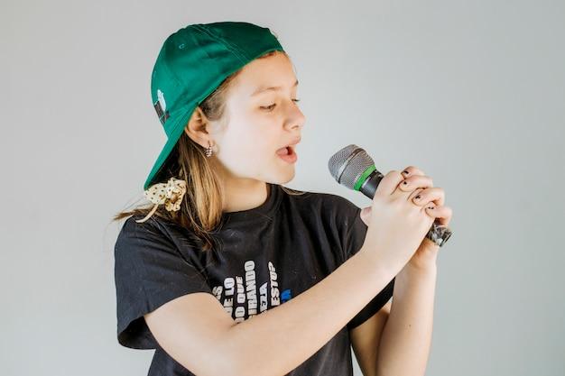 Fille chantant la chanson avec microphone sur fond gris Photo gratuit