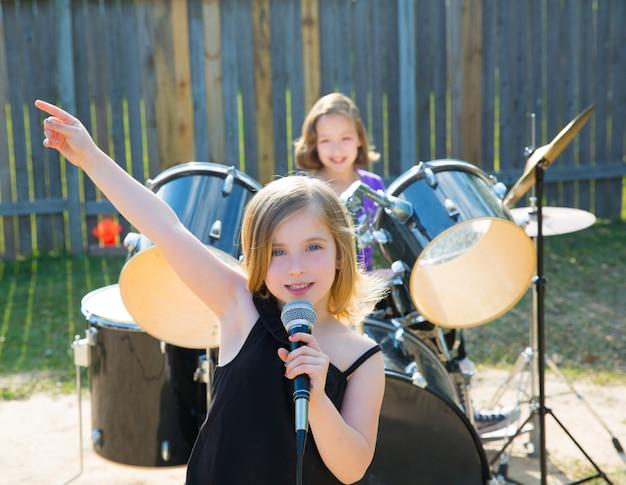 Fille chanteuse enfants chantant jouer du groupe live dans la cour Photo Premium
