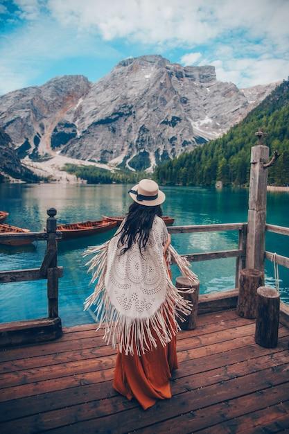 Fille avec chapeau de paille sur le lac turquoise avec des bateaux en bois dans les montagnes. Photo Premium