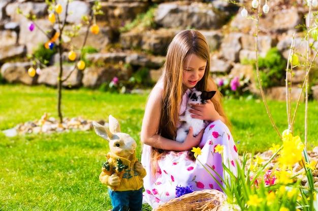 Fille sur la chasse aux oeufs de pâques avec vivant lapin de pâques Photo Premium