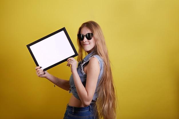 Fille cheveux longs dans des verres avec cadre vide sur fond jaune Photo Premium