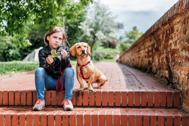 Fille avec le chien en plein air Photo Premium