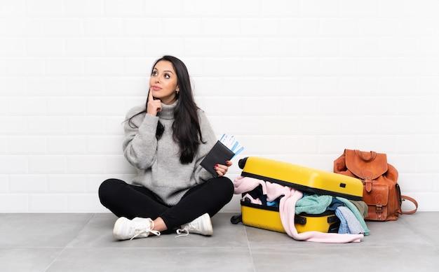 Fille Colombienne Voyageur Avec Une Valise Pleine De Vêtements Assis Sur Le Sol En Pensant à Une Idée Photo Premium